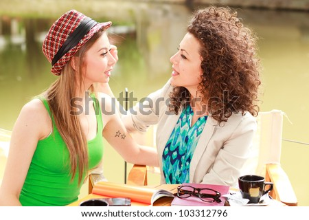 gay women couple drinking coffee and chatting on the river side terrace