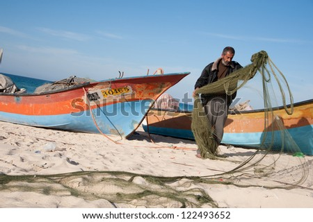 GAZA, PALESTINIAN TERRITORY - DECEMBER 2: Fisherman Nassar Abu Odeh untangles his nets on the beach near Khan Younis, Gaza, December 2, 2012. - stock photo