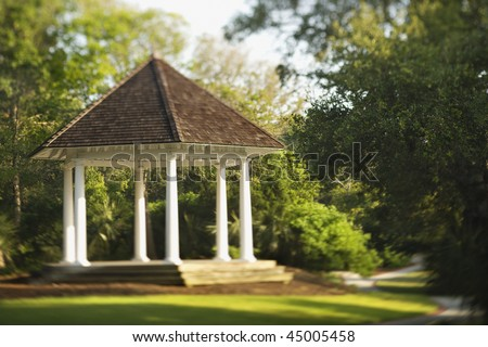 Gazebo is surrounded by park greenery. Horizontal shot. - stock photo