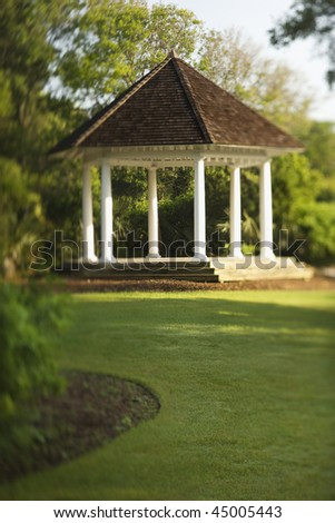Gazebo is surrounded by park greenery. Vertical shot. - stock photo