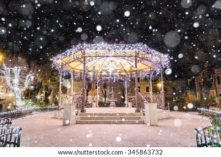 Gazebo on a village square festively lit up for Christmas with snow - stock photo