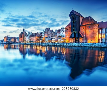 Gdansk old town and famous crane, Polish Zuraw. View from Motlawa river, Poland at romantic sunset, night. The city also known as Danzig and the city of amber. - stock photo