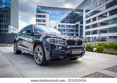 GDANSK, POLAND - SEPTEMBER 3 , 2015: New model BMW X6 in dark blue against modern design buildings in Gdansk. BMW is a German automobile, motorcycle and engine manufacturing company founded in 1916. - stock photo