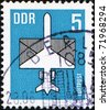 GDR - CIRCA 1982: A stamp printed in GDR (East Germany) shows airmail - the plane on the background of the envelope, circa 1982 - stock photo