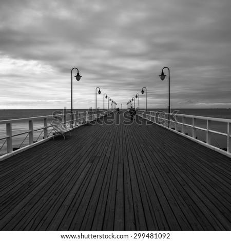 Gdynia Orlowo pier. Black and white photo of Baltic sea shore seascape. - stock photo