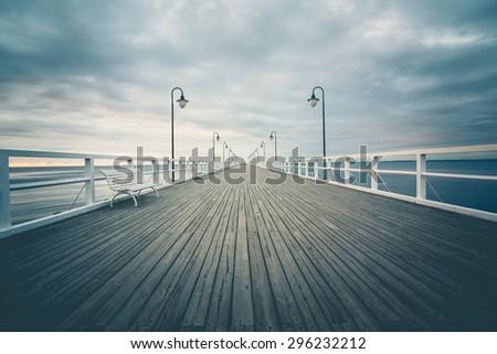 Gdynia Orlowo pier. Vintage photo of Baltic sea shore seascape.People while walking - stock photo