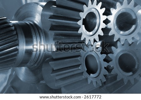 gear assembly from gearbox in blue tone, mirrored against titanium - stock photo