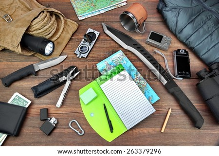 Gear laid Out For Backpacking Trip On  Table. Items Include Rope Bag Backpack  Raincoat Vest Notepad Compass Wallet Money Binoculars Knife Machete Searchlight Flashlight Rope Pen Pencil Mug Map - stock photo