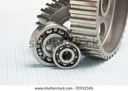 gears and bearings on graph paper - stock photo