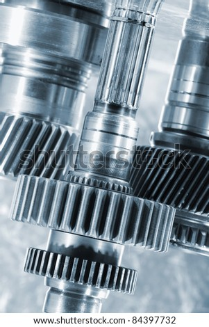 gears, pinions and wheels, titanium and steel against brushed aluminum background - stock photo