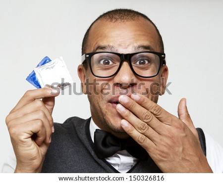 Geek holding some condoms, concept of sexual health embarrassment