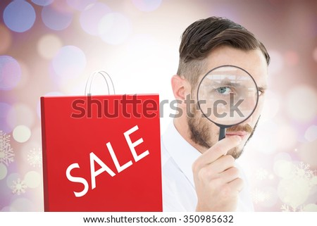 Geeky businessman looking through magnifying glass against glowing christmas background - stock photo