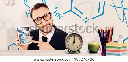 Geeky businessman pointing to calculator against desk - stock photo