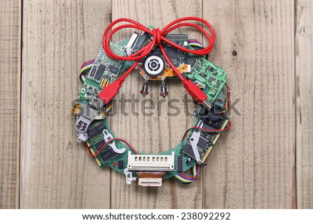 geeky christmas wreath made by old computer parts hanging on wooden door, computer parts recycling idea, christmas card design - stock photo