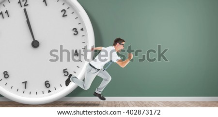 Geeky happy businessman running mid air in front of a clock - stock photo