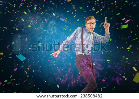 Geeky hipster dancing to vinyl against colourful fireworks exploding on black background - stock photo