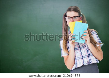 Geeky hipster hiding her face behind notepad against green chalkboard - stock photo