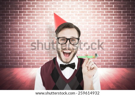 Geeky hipster in party hat with horn against grey background with vignette - stock photo