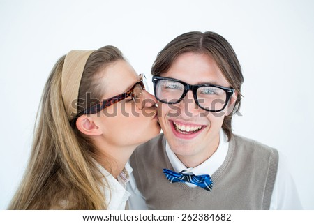 Geeky hipster kissing her boyfriend on white background - stock photo