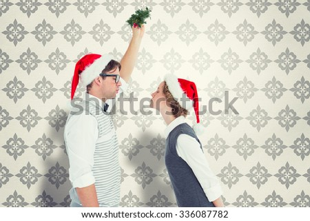 Geeky hipster kissing under mistletoe against grey wallpaper - stock photo