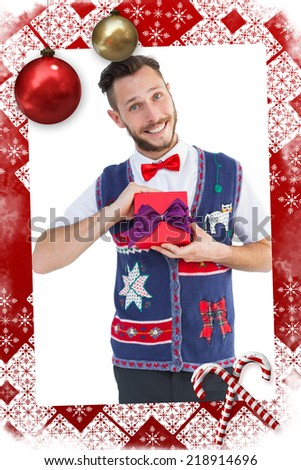 Geeky hipster offering christmas gift against christmas themed page - stock photo