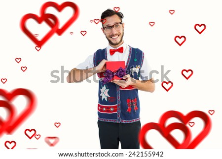 Geeky hipster offering christmas gift against hearts - stock photo