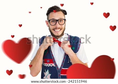 Geeky hipster wearing christmas vest against hearts - stock photo