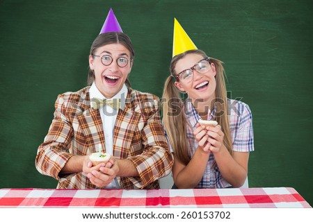 Geeky hipsters celebrating birthday against green chalkboard - stock photo