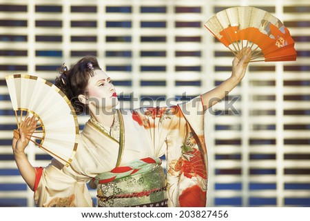 geisha dancing with fans against white gate - stock photo