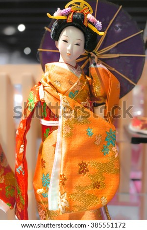Geisha Doll with selective focus on her orange Kimono, Japanese Traditional Female Dress, holding umbrella, abstract blur background - stock photo