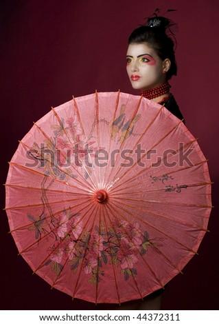 Geisha holding a beautiful red umbrella. studio shot - stock photo