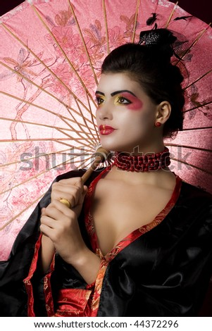 Geisha in studio with extreme makeup. Studio shot - stock photo