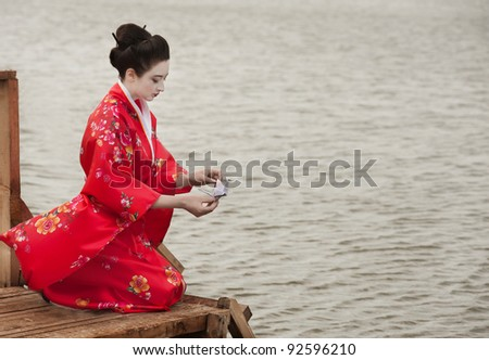 Geisha launches origami bird - stock photo