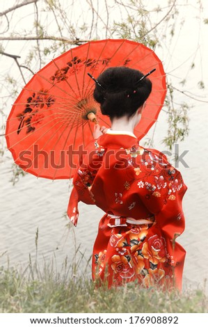 Geisha with red umbrella at the river bank (back view) - stock photo