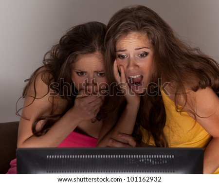 Gemini sisters watching a horror movie on TV - stock photo
