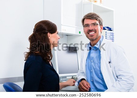 General practitioner in doctors office seeing patient - stock photo