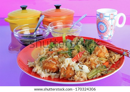 General Tso's Chicken in red plate reflecting in glass-top table in Chinese Restaurant.  Purple and pink background with colorful serving dishes. - stock photo