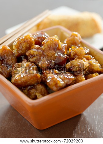general tsos chicken in a bowl with egg roll in background - stock photo