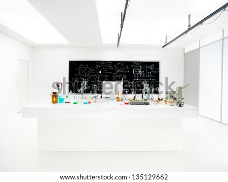 general-view of a chemistry laboratory with a lab table containing colorful liquids and lab tools and a blackboard on the background - stock photo