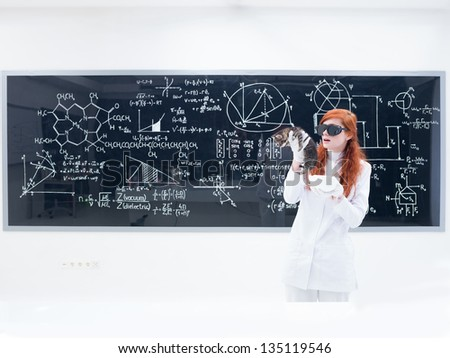 general-view of a pretty girl student in a chemistry lab wearing black glasses and holding a lab pot while analyzing a cat and a blackboard on the background - stock photo