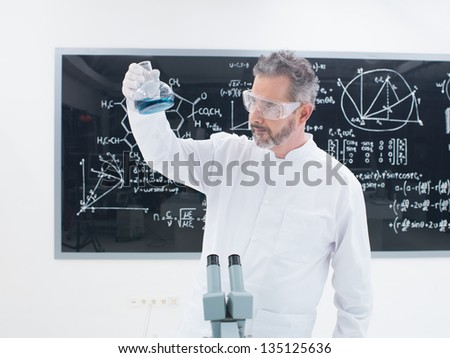 general-view of a scientist in a chemistry lab analyzing colorful substances around laboratory tools and  with a blackboard on the background