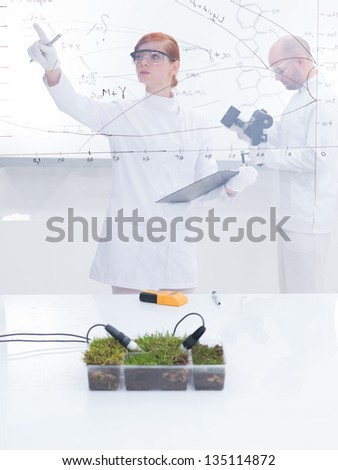 general-view  of a student in a chemistry lab analyzing graphics and her teacher analyzing under microscope in the background of a transparent board around lab table with a box of grass on it - stock photo