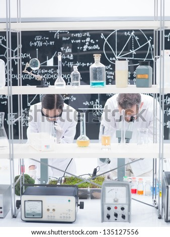 general-view of two researchers i a chemistry lab analyzing under microscope on a lab table around lab tools and colorful liquids with a blackboard with formulas on the background - stock photo