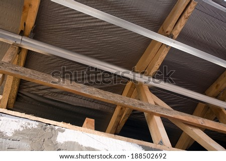 General view of wooden and metal support profiles for finishing material of the outer wall of the building, made with their own hands - stock photo