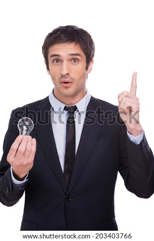 Generating creative ideas.  Handsome young man in formalwear holding light bulb and pointing up while standing isolated on white background