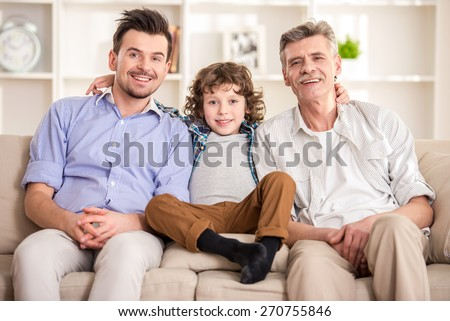 Generation portrait. Grandfather, father and son sitting on sofa. - stock photo