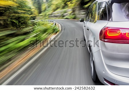 Generic car form the future driving fast on a mountain road - stock photo