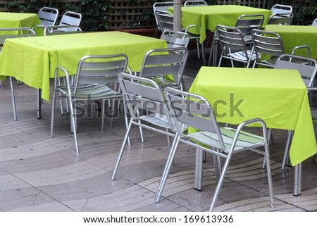 Generic contemporary restaurant in Barcelona, Spain. Outdoor tables with stainless steel chairs. - stock photo