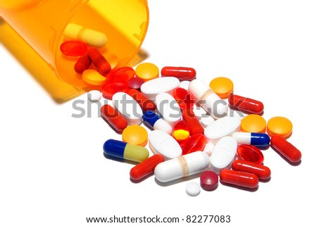 Generic prescription medicine medication pills spilled out of a pharmaceutical amber bottle as a metaphor for a drug abuse cocktail and dangerous overdose - stock photo
