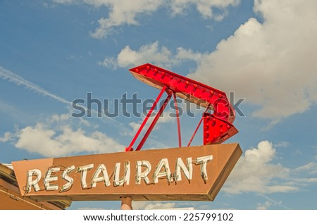Generic restaurant sign with neon tubes on Route 66.  The red arrow has bulbs in it. - stock photo